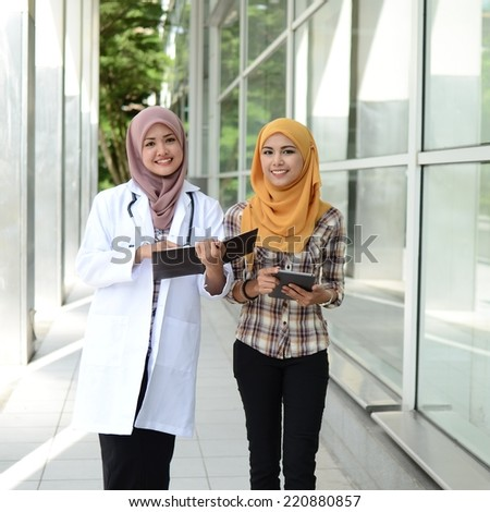 Confident Muslim doctor teach and help medical student together