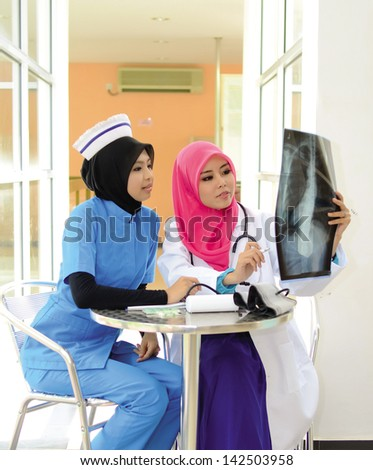 Confident Muslim female doctor and nurse in head scarf smile - stock photo