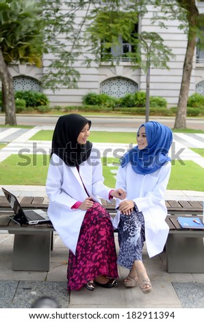 Confident Muslim medical student busy conversation at park - stock photo