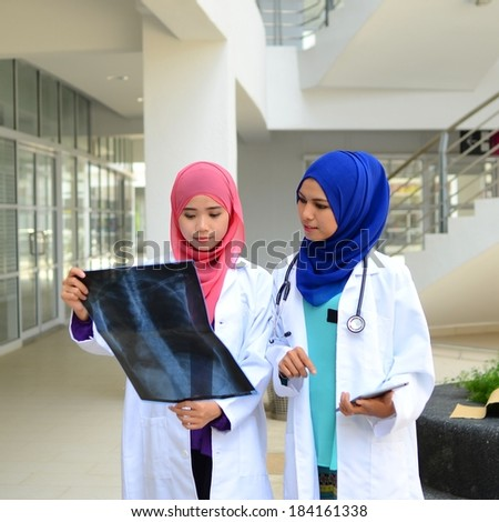 Confident  Muslim medical student busy doctor looking at patient's x-ray