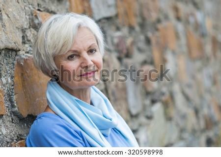 confident natural senior women posing at brick wall - stock photo