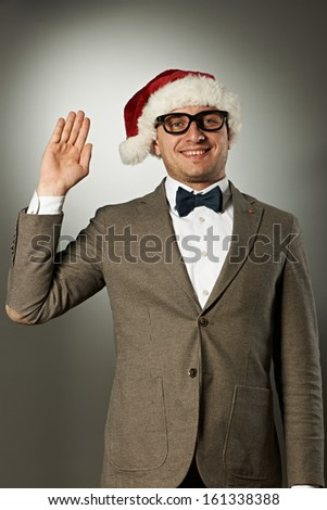 Confident nerd in Santa Claus hat and bow tie celebrates Christmas - stock photo