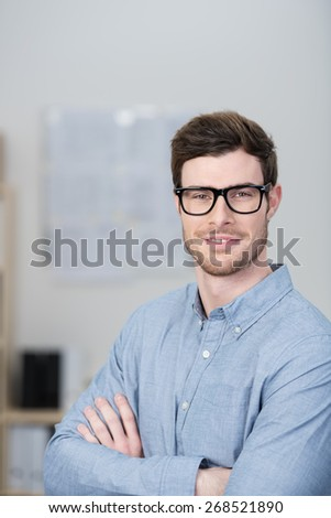 Confident nerdy young businessman wearing black framed glasses peering short sightedly at the camera with crossed arms - stock photo