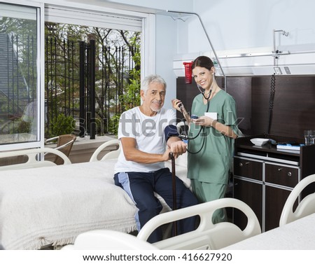 Confident Nurse Checking Blood Pressure Of Patient In Rehab Cent - stock photo