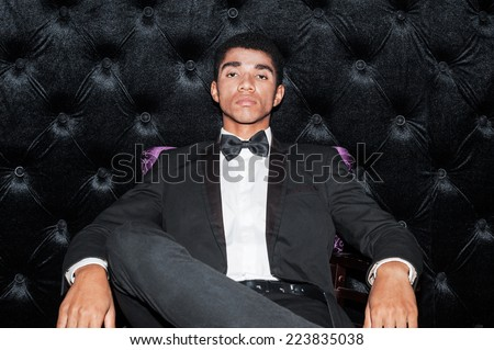 Confident of being the best. Fashionable young Afro-American man sitting on the chair putting one leg on another  - stock photo