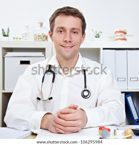 Confident physician during consultation hour in doctor's office - stock photo