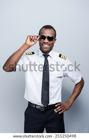 Confident pilot. Confident African pilot in uniform adjusting his eyeglasses and smiling while standing against grey background - stock photo