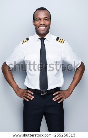 Confident pilot. Confident African pilot in uniform holding hand on hip and smiling while standing against grey background