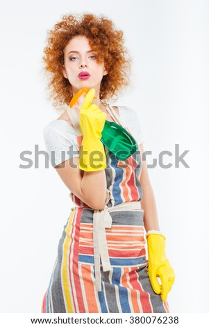 Confident playful young woman in striped apron and yellow gloves posing with spray bottle over white background - stock photo