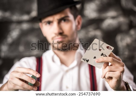 Confident poker player. Serious, handsome young man in shirt and suspenders is sitting at the poker table and holding cards and chips. - stock photo