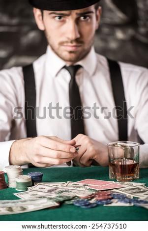 Confident poker player. Serious young man in shirt, hat and suspenders is sitting at the poker table with cards, chips and a glass of whisky. - stock photo
