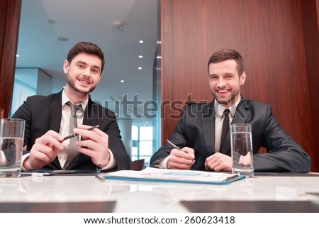 Confident professionals. Low angle of two cheerful business people in formal wear looking at camera and smiling while having business meeting in the office - stock photo