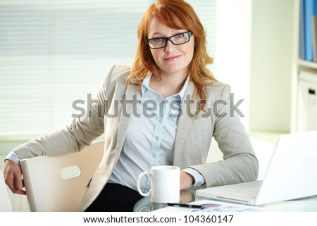 Confident red-haired business woman smiling at camera from her workplace
