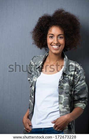 Confident relaxed African American woman standing with her hands in her pockets wearing a trendy patterned top and smiling at the camera - stock photo