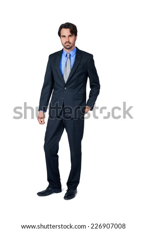 Confident relaxed business executive in a stylish suit standing smiling at the camera with his hand in his pocket, full length isolated on white