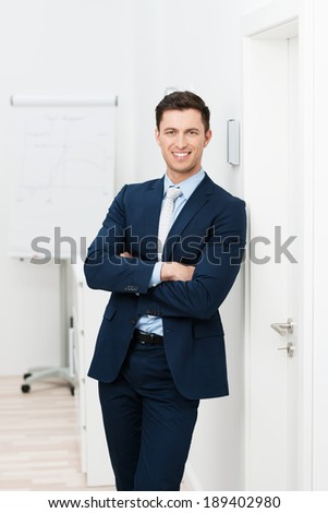 Confident relaxed young businessman in a stylish suit standing with folded arms leaning against the wall and smiling at the camera - stock photo