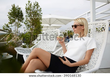 Confident rich woman dressed in trendy clothes is enjoying water with lemon during work on portable touch pad. Young hipster girl is using digital tablet, while she is relaxing in modern restaurant - stock photo