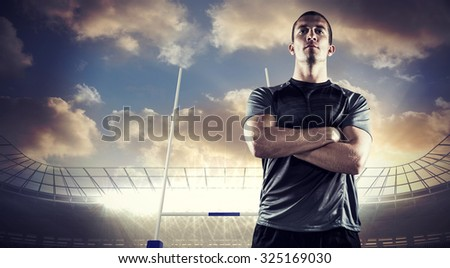 Confident rugby player with arms crossed against rugby stadium - stock photo