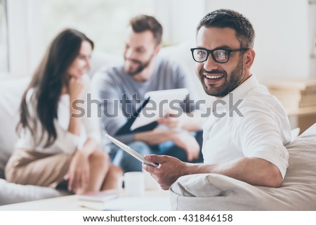 Confident sales manager. Cheerful mature man holding digital tablet and looking over shoulder while another man and woman sitting in the background   - stock photo