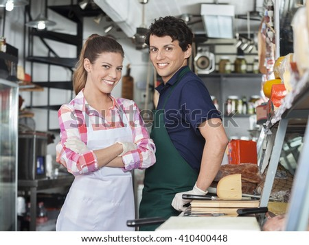 Confident Salespeople At Counter In Cheese Shop - stock photo
