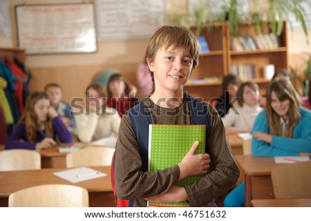 Confident schoolboy is standing in front of class. Space for cropping