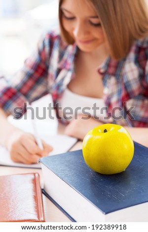 Confident schoolgirl. Top view of cheerful teenage girl studying while sitting at the desk - stock photo