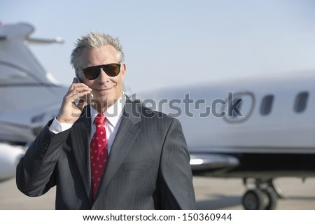 Confident senior businessman using cell phone with private jet in background - stock photo