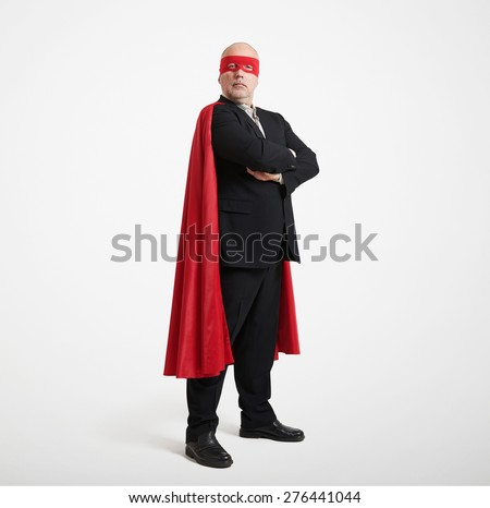 confident senior businessman wearing like super hero in red mask and cloak over light grey background - stock photo