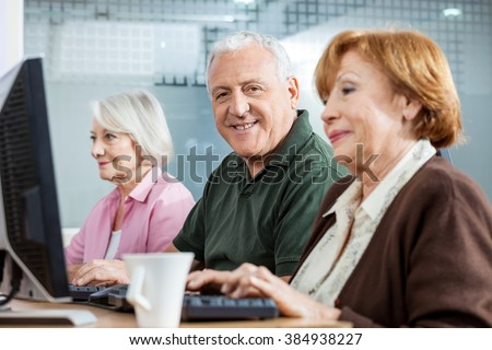 Confident Senior Man With Female Friends In Computer Class
