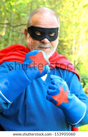 Confident senior super hero kicking fist together