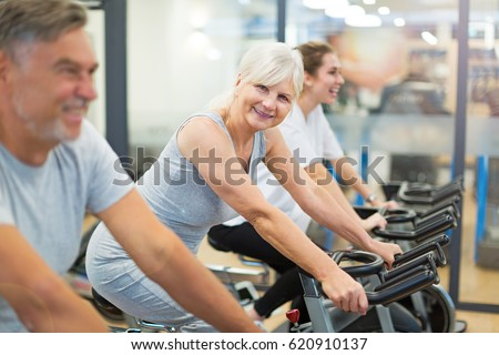 Confident seniors on exercise bikes