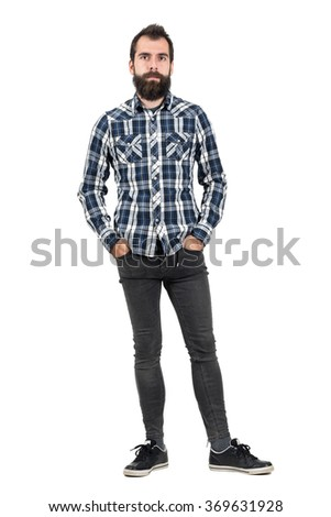 Confident serious hipster in plaid tartan blue shirt with hands in pockets. Full body length portrait isolated over white studio background.