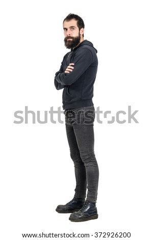 Confident serious punker wearing old worn boots and black hooded sweatshirt looking at camera. Full body length portrait isolated over white studio background.
