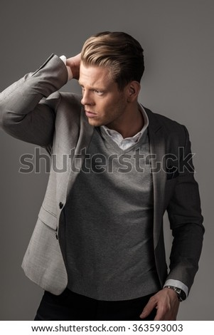 Confident sharp dressed man in grey suit