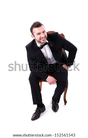 Confident Smart  Looking Man Smiling, sitting a chair, wearing tuxedo, isolated on white background