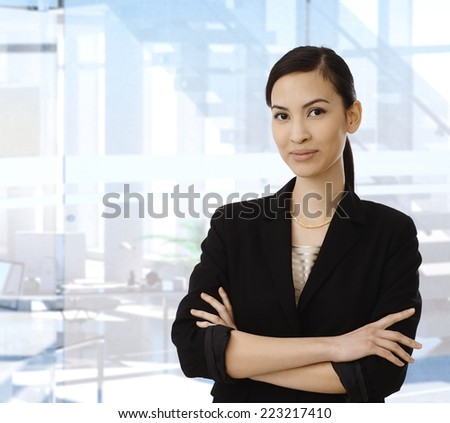Confident smiling asian businesswoman standing in front of bright business office with arms crossed, looking at camera. Copyspace. - stock photo