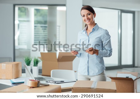 Confident smiling business woman moving in her new office, she is unpacking boxes and using a digital tablet - stock photo