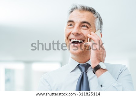 Confident smiling businessman having a phone call on his smart phone - stock photo