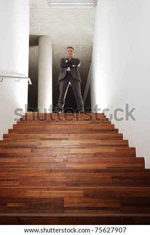 Confident smiling businessman in grey suit standing at top of office staircase looking down, symbolizing business success, achievement or successful career. - stock photo