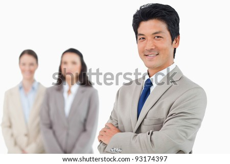 Confident smiling businessman with his team behind him against a white background