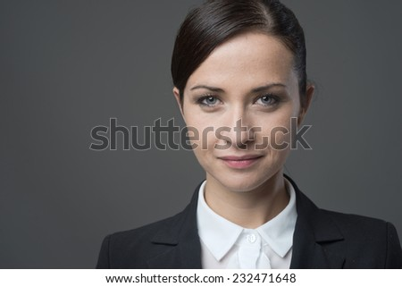 Confident smiling businesswoman smiling and posing on gray background. - stock photo