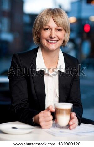 Confident smiling corporate lady holding coffee mug and posing. - stock photo