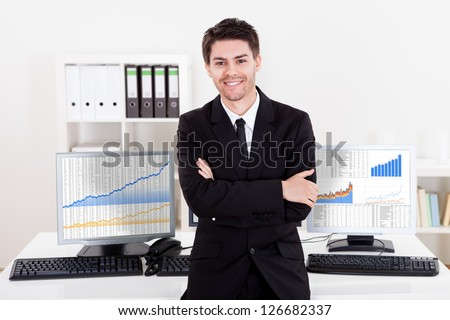Confident smiling stock broker sitting on the edge of his desk surrounded by graphs and analytics indicating a successful bull market
