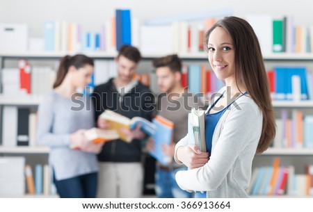 Confident smiling student girl posing in the library, holding books and looking at camera, learning and education concept