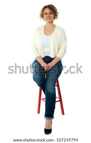 Confident smiling woman sitting on stool and looking at camera - stock photo