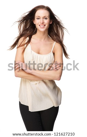 Confident smiling young beautiful caucasian woman with crossed arms. her hair is blowing in the wind. Isolated on white background - stock photo
