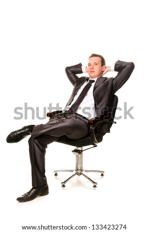 Confident smiling young businessman relaxing on a chair isolated on white
