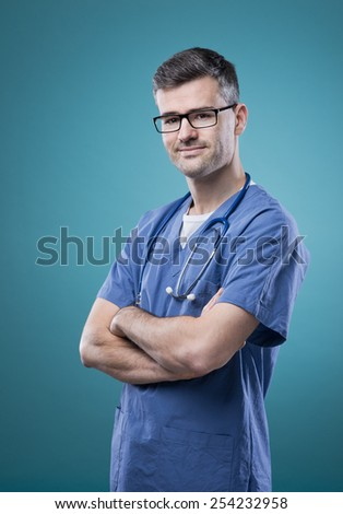 Confident smiling young doctor posing with arms crossed - stock photo
