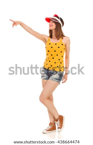 Confident smiling young woman in yellow dotted shirt, jeans shorts, red sun visor and brown sneakers standing, pointing and looking away. Full length studio shot isolated on white. - stock photo