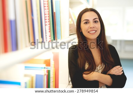 Confident smiling young woman standing alongside a bookcase full of books with folded arms looking at the camera with a friendly smile